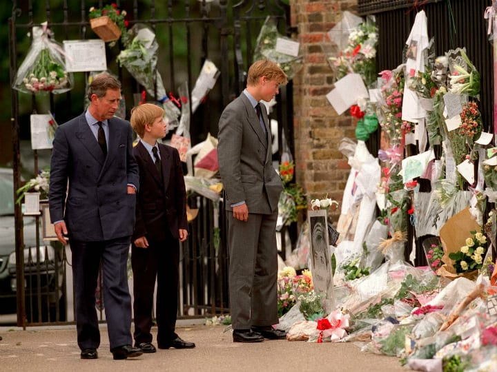 Prince Charles with sons William and Harry looking at memorial flowers