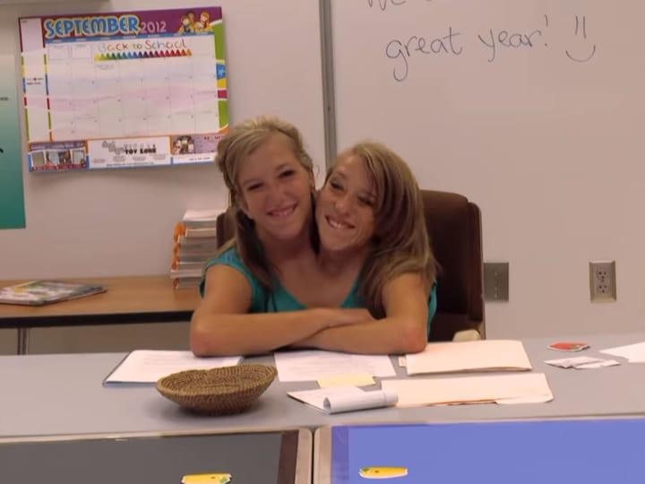 in the classroom, smiling, happy twins, Brittany and Abby