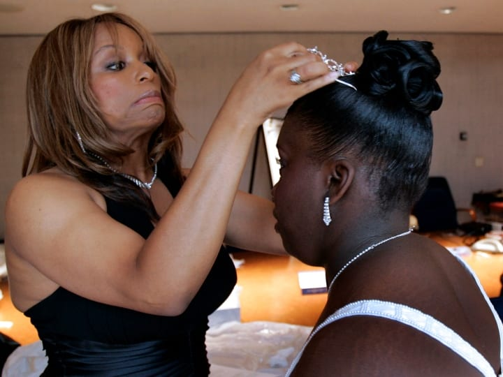 "Kenadie Cobbin, director of the HerShe Group, delicately places a tiara on one of the ""debutantes"" preapring for the the Cinderella Ball, designed to prepare young women for emancipation from the foster care system at the Los Angeles Museum of Natural History in Los Angeles, July 29, 2006. The HerShe group runs the event. The girls spent two weeks at Pepperdine Univeristy being trained in life skills,personal and social development."