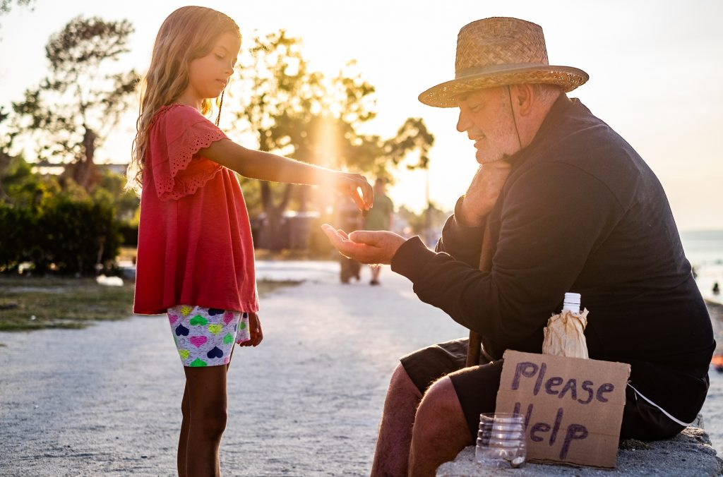Beautiful little girl helping homeless men by giving him a coins