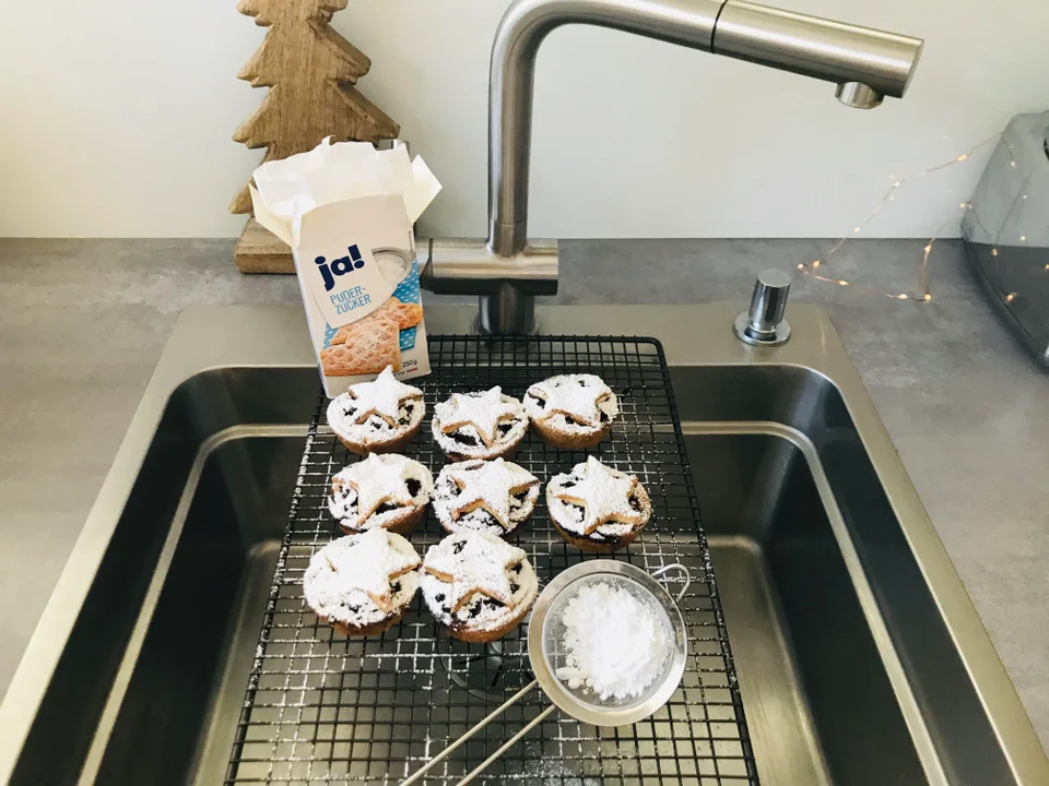 Cookies sit on a wire rack over a sink. They are being dusted with powdered sugar
