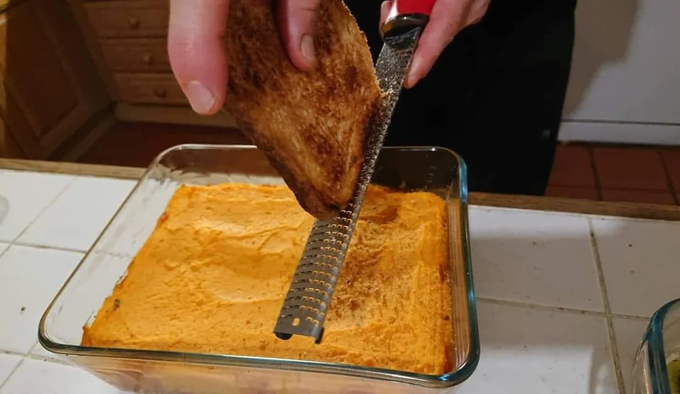 Grating toast over a dish