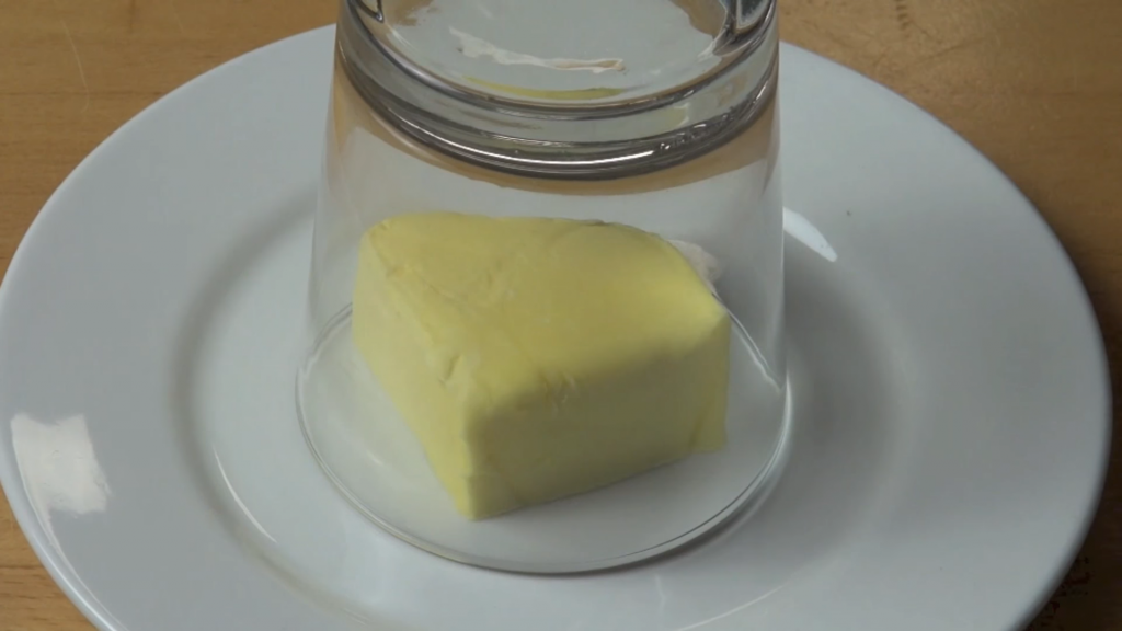 A pat of butter sits on a plate with an upturned cup on top of it
