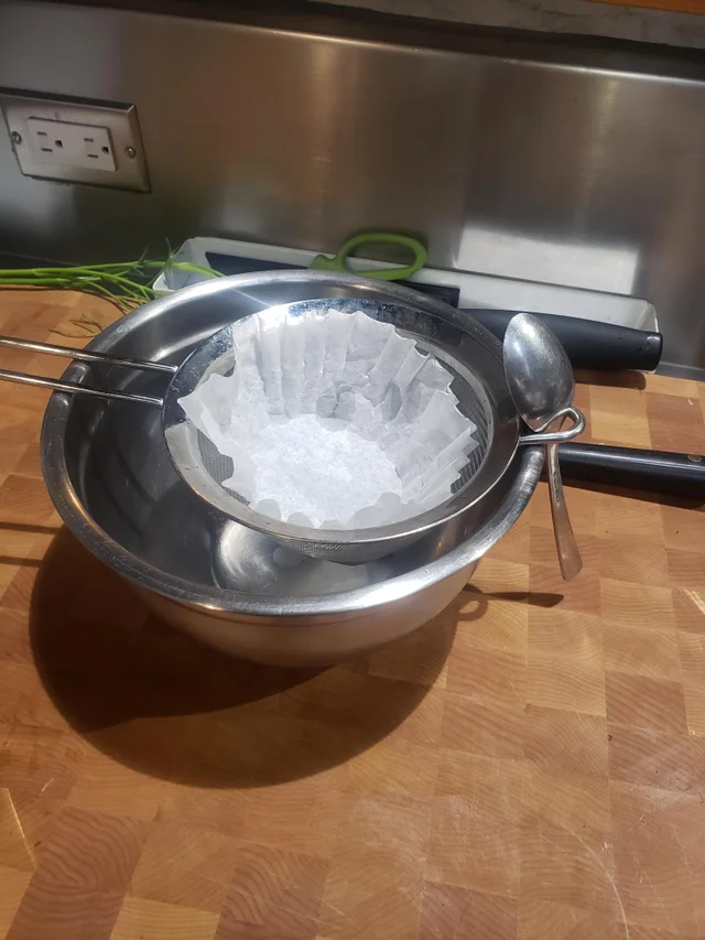 A strainer sits on top of a mixing bowl, a spoon holds the strainer in place